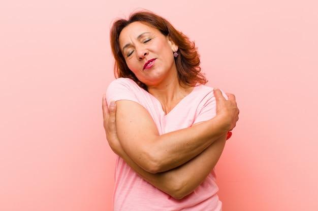 Mulher de meia idade se sentindo apaixonado, sorrindo, abraçando e abraçando a si mesmo Foto Premium