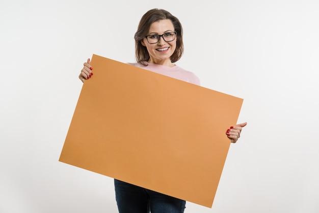 Mulher de meia idade sorridente com outdoor folha laranja Foto Premium