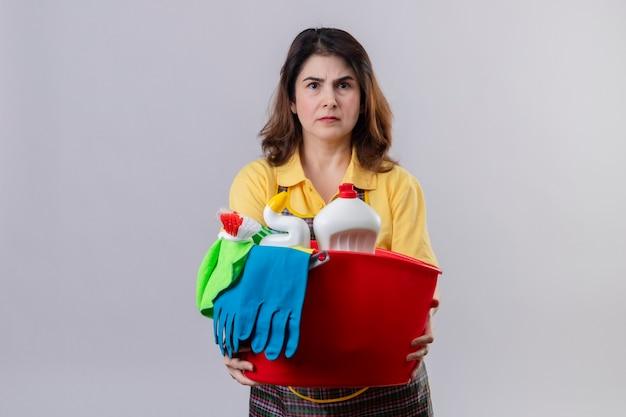 Mulher de meia-idade usando avental segurando um balde com ferramentas de limpeza e parecendo descontente com o rosto carrancudo em pé sobre uma parede branca Foto gratuita