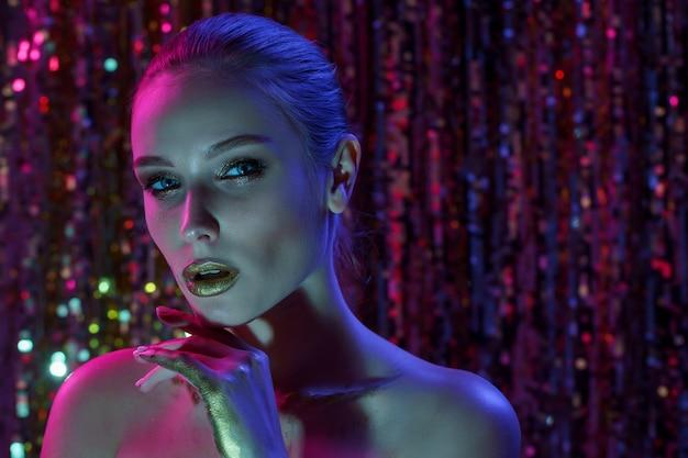 Mulher de modelo de alta moda em luzes de néon brilhantes coloridas posando no estúdio, boate. retrato de menina bela dançarina sedutora sexy em uv. Foto Premium