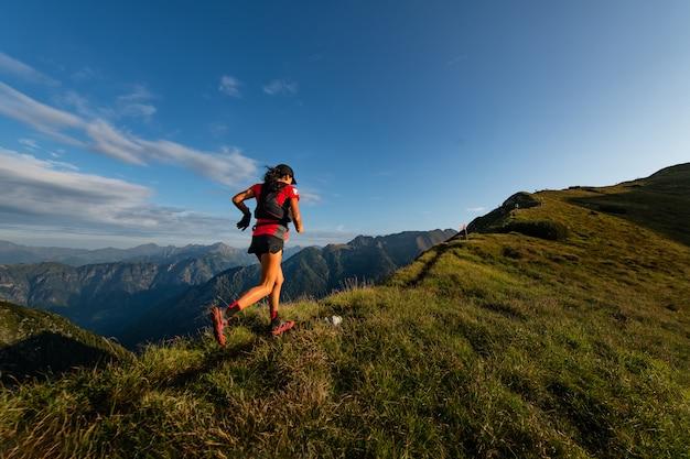 Mulher de montanha desportiva passeios na trilha durante a trilha de resistência Foto Premium