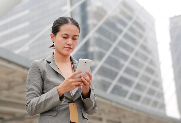 Mulher de negócio bonita que trabalha em um smartphone em suas mãos ao ar livre. Foto Premium