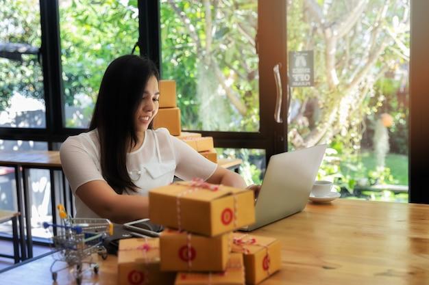 Mulher de negócio com vendas em linha e envio do pacote em seu escritório domiciliário. Foto Premium