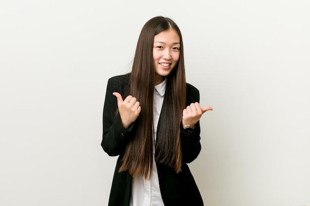 Mulher de negócio consideravelmente chinesa nova que levanta ambos os polegares acima, sorrindo e confiantes. Foto Premium