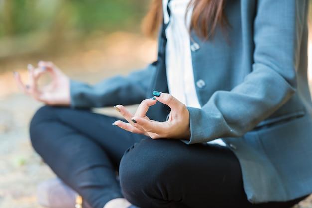 Mulher de negócio da ioga que faz a meditação com espiritual no parque. Foto Premium