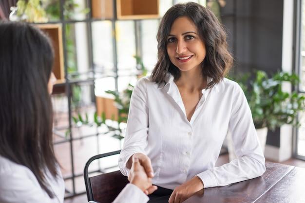Mulher de negócio de sorriso que agita as mãos com o sócio no café. Foto gratuita