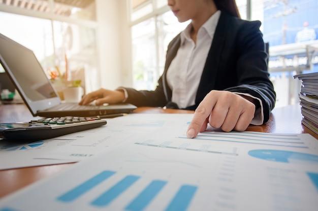 Mulher de negócio em trabalhar com relatórios financeiros e computador portátil no escritório. Foto Premium