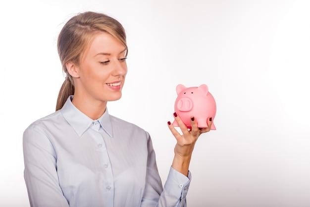 Mulher de negócio feliz com suas economias em um cofrinho Foto gratuita