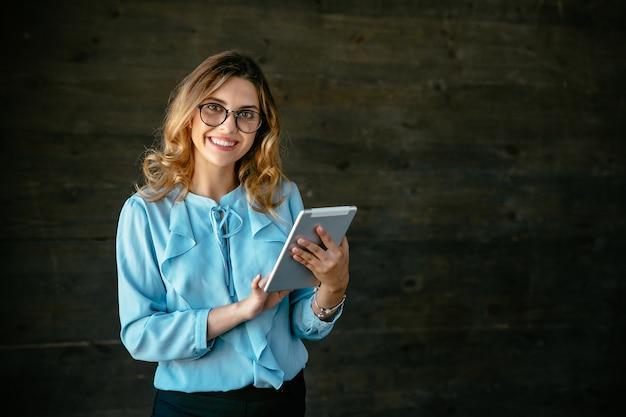 Mulher de negócio nova bonita feliz que está com a tabuleta, extensamente sorrindo. Foto gratuita