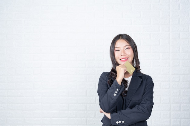 Mulher de negócio que prende um cartão separado do dinheiro, parede de tijolo branca gestos feitos com língua de sinais. Foto gratuita