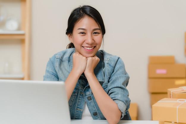 Mulher de negócio que sente feliz sorrindo e olhando à câmera ao trabalhar em seu escritório em casa. Foto gratuita