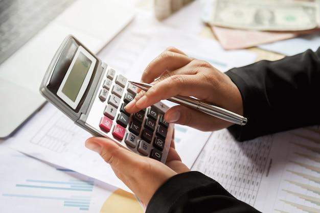 Mulher de negócio que usa a calculadora para trabalhar no escritório. conceito de finanças e contabilidade Foto Premium