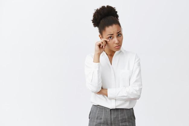 Mulher de negócios afro-americana sombria e triste chorando, chorando e enxugando as lágrimas Foto gratuita