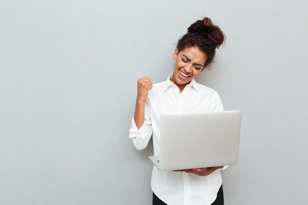 Mulher de negócios alegre fazer gesto vencedor. Foto gratuita