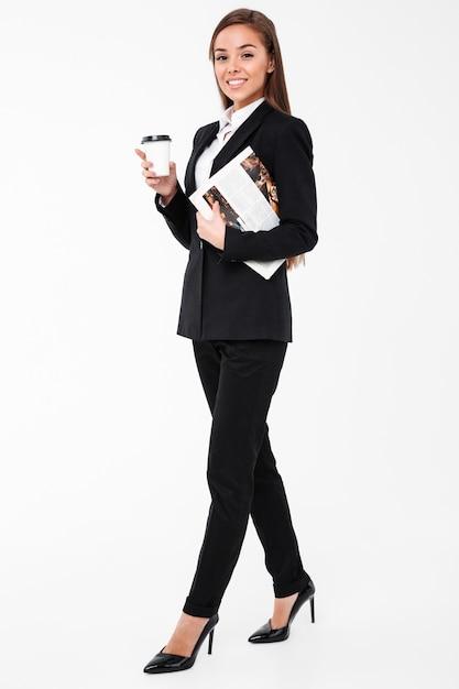 Mulher de negócios alegre segurando jornal bebendo café. Foto gratuita