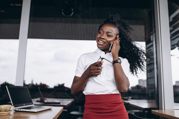 Mulher de negócios americano africano com computador e telefone em um café Foto gratuita