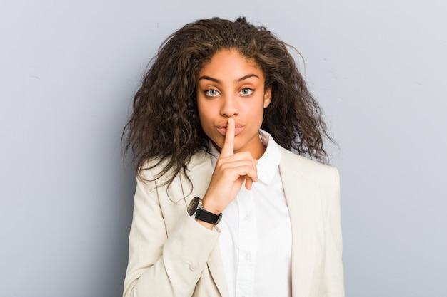 Mulher de negócios americano africano jovem mantendo um segredo ou pedindo silêncio. Foto Premium