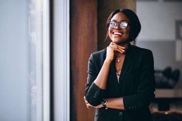 Mulher de negócios americano africano pela janela Foto gratuita