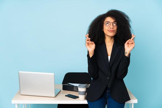 Mulher de negócios americano africano trabalhando em seu local de trabalho com os dedos cruzando e desejando o melhor Foto Premium