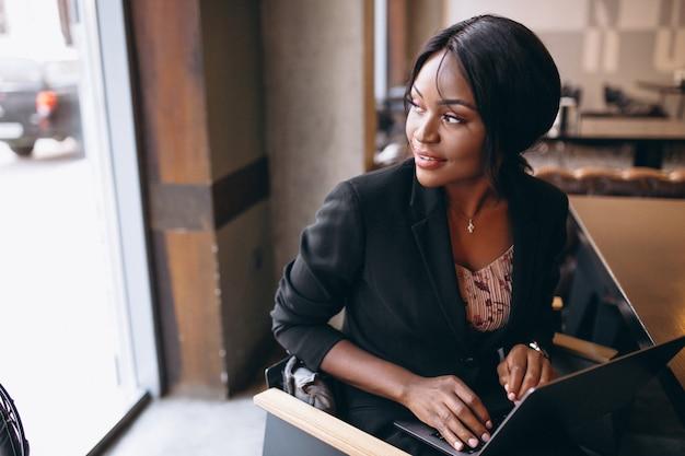 Mulher de negócios americano africano trabalhando em um computador em um bar Foto gratuita