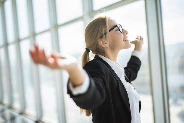 Mulher de negócios animado segurar as mãos para cima braços erguidos comemorar vitória no escritório moderno Foto gratuita