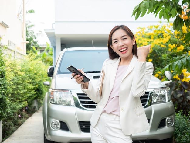 Mulher de negócios asiática que usa o telefone esperto contra um carro. Foto Premium