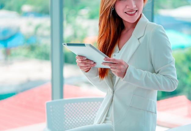 Mulher de negócios asiática que usa uma tabuleta digital que está na frente das janelas no edifício da cidade. Foto Premium