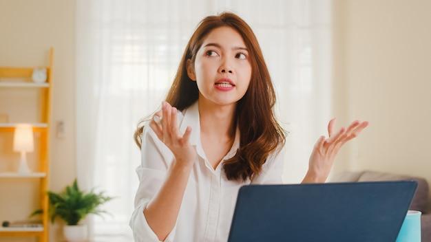 Mulher de negócios asiática usando laptop fala com colegas sobre o plano de videochamada enquanto trabalha em casa na sala de estar. auto-isolamento, distanciamento social, quarentena para prevenção do coronavírus. Foto gratuita
