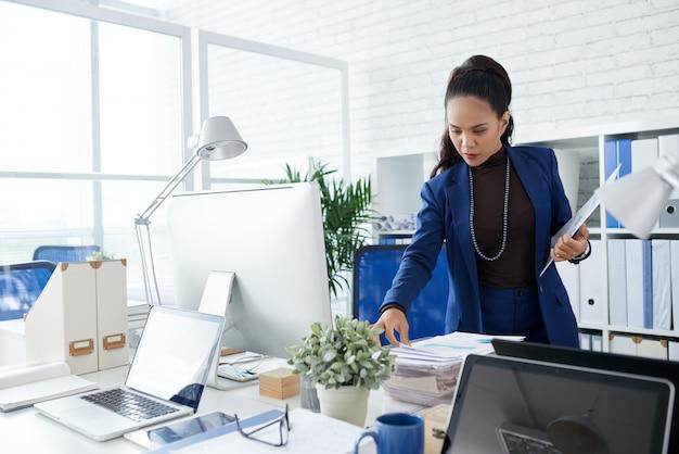 Mulher de negócios asiático em pé no escritório e olhando para a pilha de documentos na mesa Foto gratuita