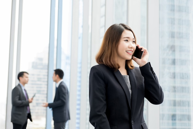 Mulher de negócios asiático falando no celular no corredor do prédio de escritórios Foto Premium