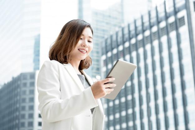 Mulher de negócios asiático usando computador tablet ao ar livre no prédio de escritórios de desfoque Foto Premium