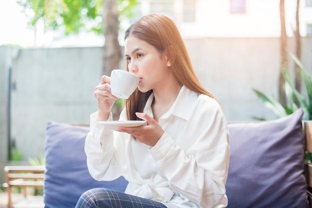 Mulher de negócios asiáticos é beber café da manhã na cafeteria Foto Premium