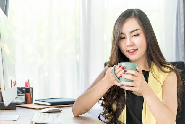 Mulher de negócios asiáticos feliz com xícara de café Foto Premium