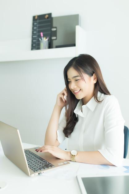 Mulher de negócios asiáticos jovens falando no telefone celular e sorrindo Foto Premium
