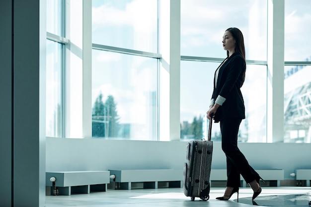 Mulher de negócios asiáticos jovens no aeroporto com saco de carrinho de bagagem, à espera de partida Foto Premium