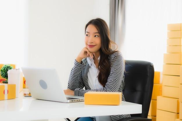 Mulher de negócios asiáticos jovens trabalhando em casa com laptop Foto gratuita