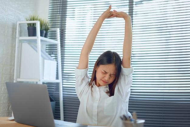 Mulher de negócios asiáticos levante sua mão acima da cabeça, para aliviar a dor e a fadiga do trabalho duro. Foto Premium