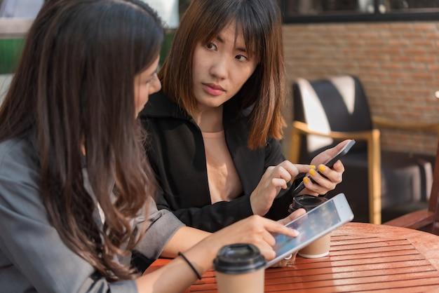 Mulher de negócios asiáticos linda trabalhando com tablet e smartphone na loja de café Foto Premium