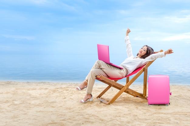 Mulher de negócios asiáticos relaxar quando se trabalha com laptop sentado na cadeira de praia na praia Foto Premium