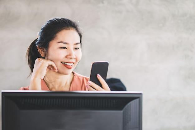 Mulher de negócios asiáticos usando telefone inteligente no trabalho Foto Premium