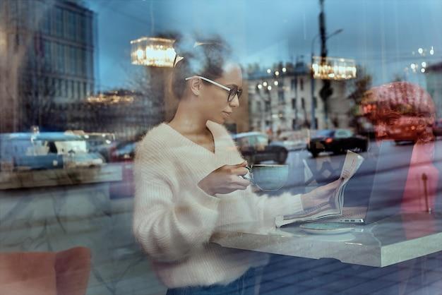 Mulher de negócios atraente em conversa de obile de espetáculos ópticos com amigo através do dispositivo de smartphone. jovem mulher positiva falando no telefone, sentado no computador portátil na cafeteria Foto Premium