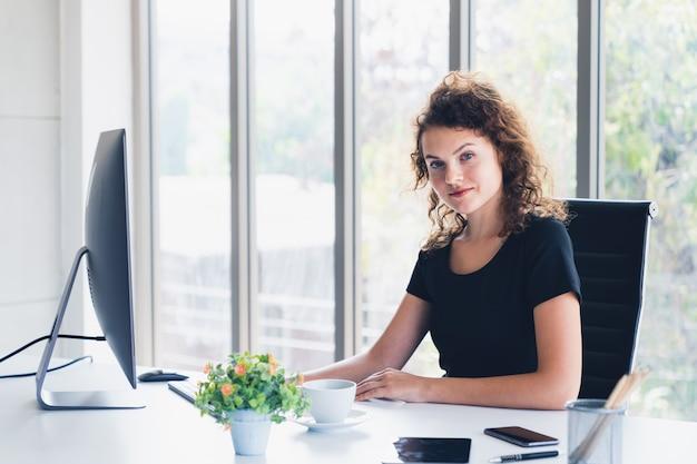 Mulher de negócios atraente jovem sorrindo enquanto está sentado na mesa do escritório Foto Premium