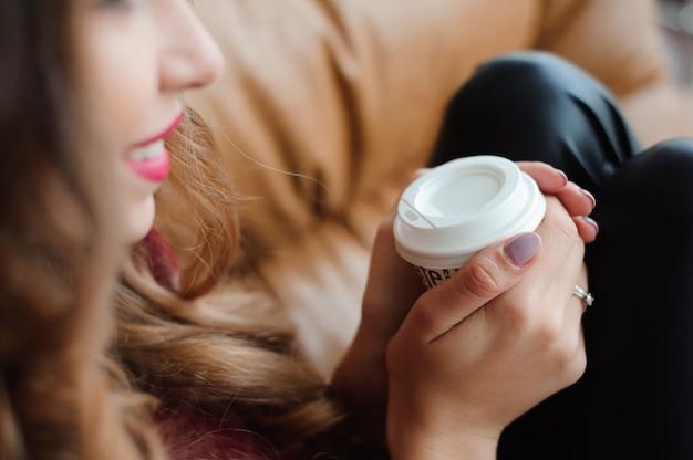 Mulher de negócios atraente tem uma pausa para café perto da janela Foto Premium