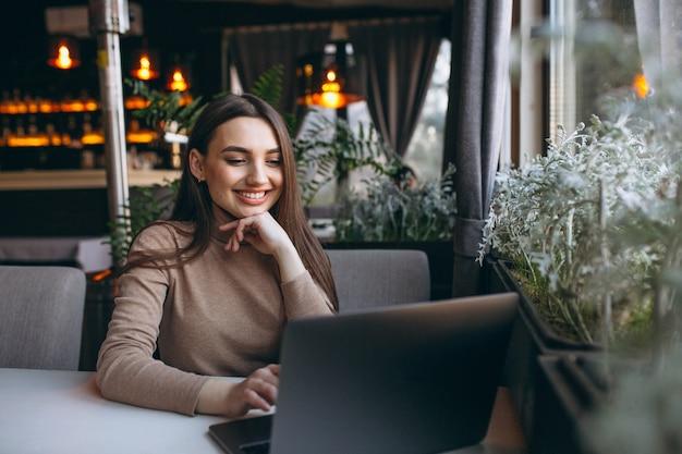 Mulher de negócios, bebendo café e trabalhando no laptop em um café Foto gratuita