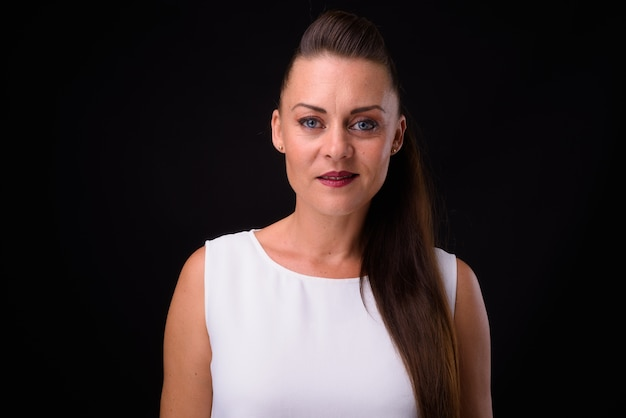 Mulher de negócios bonita madura com cabelo castanho contra uma parede preta Foto Premium