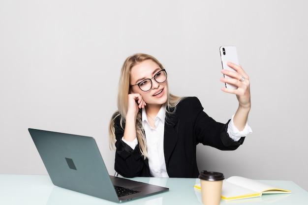Mulher de negócios bonita no escritório segurando seu telefone celular com uma mão e fazer uma chamada de vídeo na mesa de escritório Foto gratuita