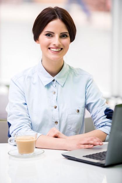 Mulher de negócios bonita nova que senta-se no café urbano. Foto Premium