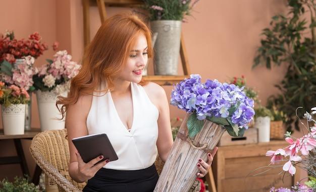 Mulher de negócios bonita sorridente verificar a ordem na loja de flores Foto Premium