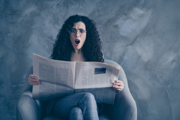 Mulher de negócios chocada e preocupada, sentada na cadeira, lendo um resumo das notícias isoladas sobre a parede cinza Foto Premium