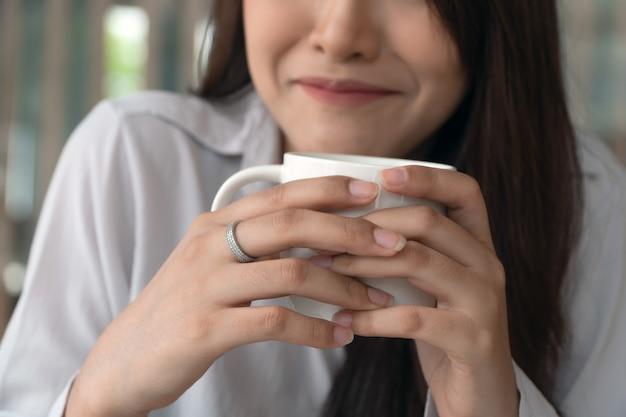 Mulher de negócios closeup está sorrindo e segurando uma xícara de café branco na cafeteria. Foto Premium